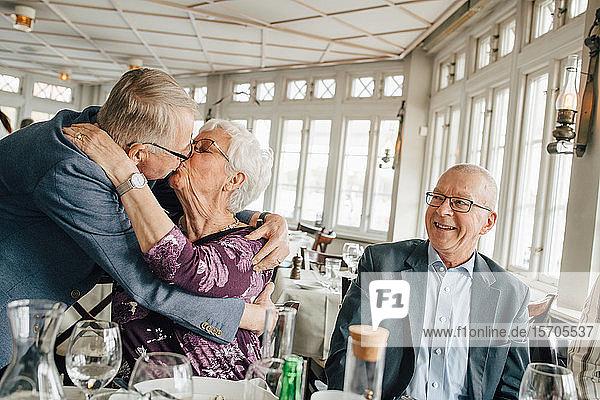 Älteres Paar küsst sich  während ein männlicher Freund im Restaurant lächelt