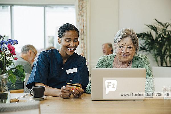 Lächelnde Pflegerin unterstützt ältere Frau beim Online-Shopping mit Kreditkarte und Laptop im Pflegeheim