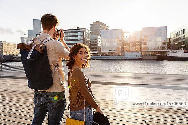 Porträt einer lächelnden Frau steht mit einem Mann  der während der Sommerferien die Stadt fotografiert