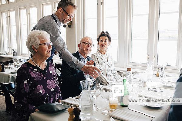 Eigentümer  der Senioren  die im Restaurant sitzen  Wasser serviert