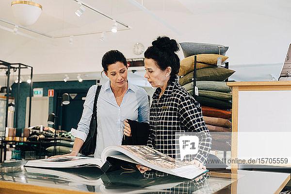Frau hilft Kunden bei der Auswahl von Tapetenmustern im Geschäft