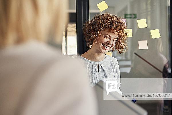 Lachende Geschäftsfrau mit Haftnotizen an Glasscheibe im Büro