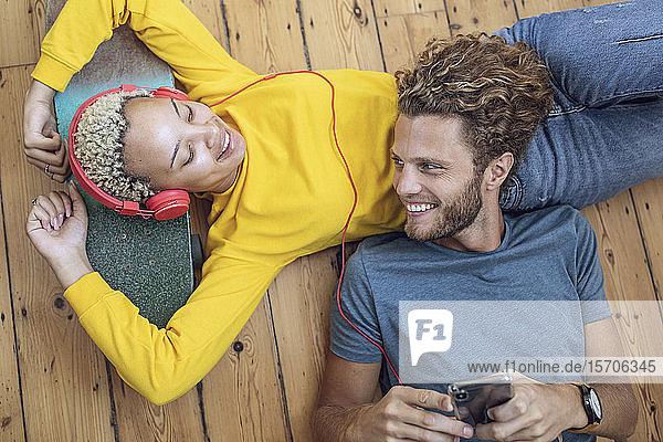 Glückliches junges Paar liegt zu Hause entspannt auf dem Boden