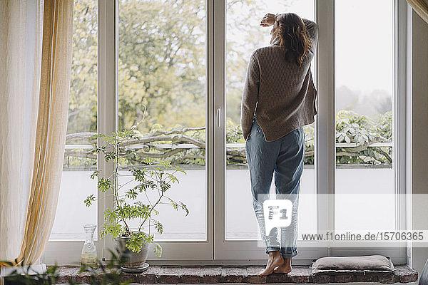 Frau schaut aus dem Fenster  Rückansicht