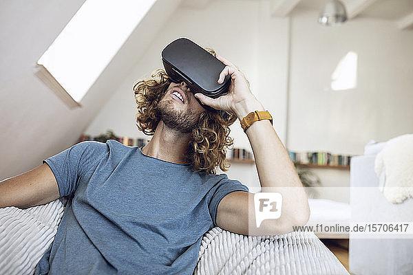 Junger Mann trägt VR-Brille zu Hause