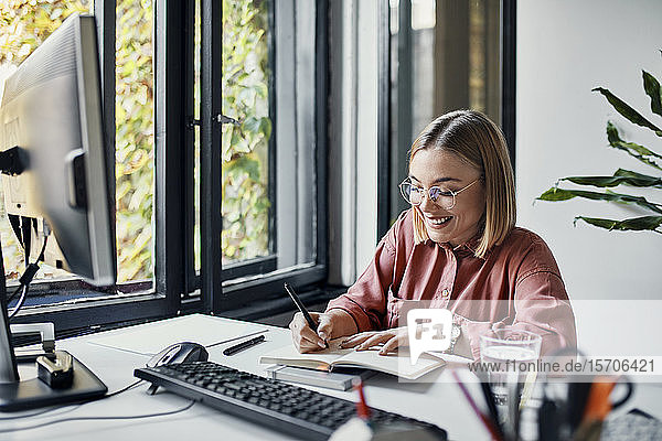 Smiling businesswoman taking notes at desk in office