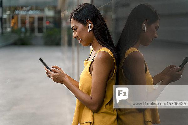 Modisch gekleidete Frau in Gelb lehnt mit Kopfhörern und Smartphone an Glasfront