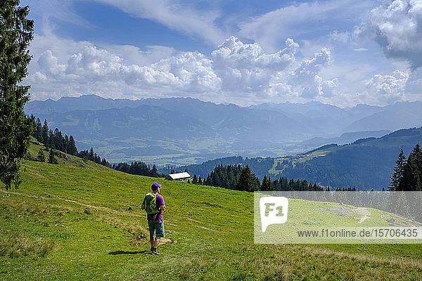Germany  Bavaria  Immenstadt  Lone hiker taking break to admire scenic landscape of Allgau Alps