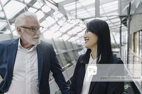 Leitender Geschäftsmann und lächelnde Geschäftsfrau in modernem Bürogebäude