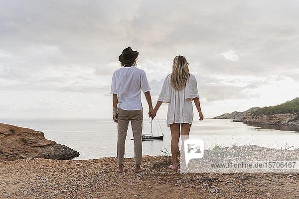 Rückansicht eines jungen verliebten Paares vor dem Meer stehend  Ibiza  Balearen  Spanien