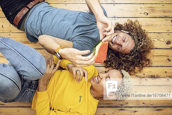Glückliches junges Paar liegt zu Hause auf dem Boden und teilt sich eine Wassermelone