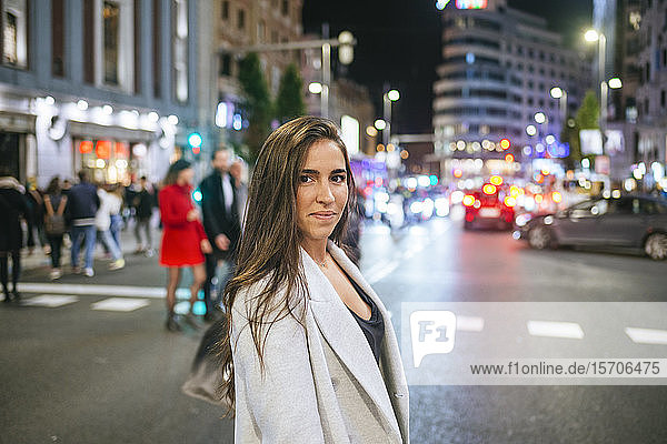 Woman walking on a street in the city at night