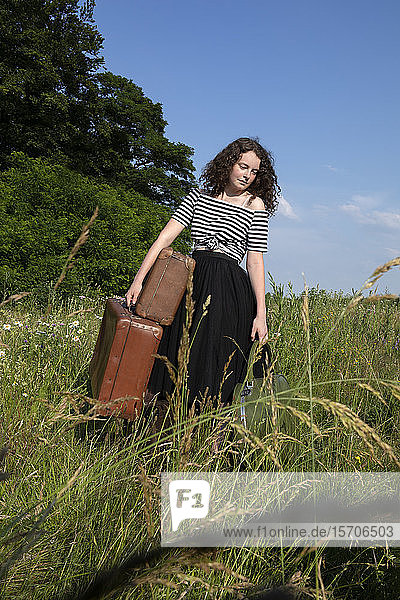 Portrait of young woman on a meadow with many suitcases