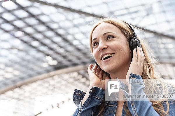 Glückliche Frau  die am Bahnhof mit Kopfhörern Musik hört  Berlin  Deutschland