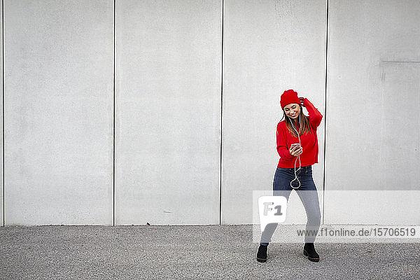 Frau mit rotem Pullover und Wollmütze  die vor einer Wand tanzt