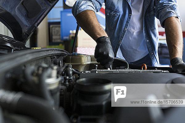 Mann mit Hemd und Handschuhen bei der Arbeit im Autoreparaturdienst und bei der Reparatur des Automotors
