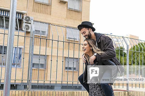 Lachende junge Frau  die ihren Freund Huckepack nimmt