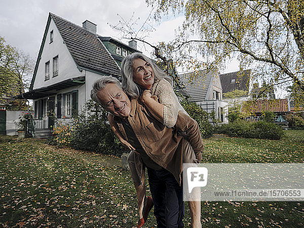 Happy senior man carrying wife piggyback in garden of their home in autumn