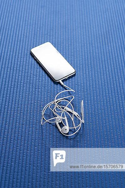 Smartphone und Kopfhörer auf blauer Trainingsmatte