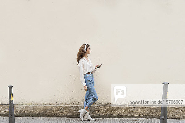 Young woman with smartphone and headphones on sidewalk