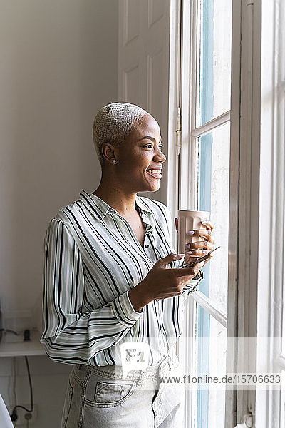 Happy woman with cell phone and coffee cup looking out of window