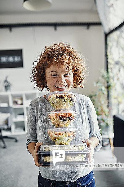 Porträt einer lächelnden Geschäftsfrau  die einen Stapel Essen zum Mitnehmen im Büro hält