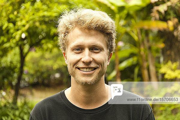 Porträt eines lächelnden jungen erdbeerblonden Mannes