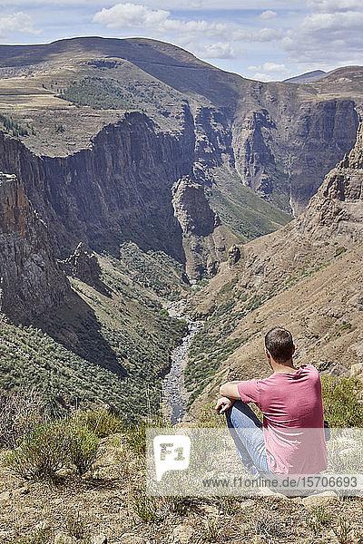 Mann sitzt auf einem Hügel an den Maletsunyane-Fällen und genießt die Aussicht  Lesotho