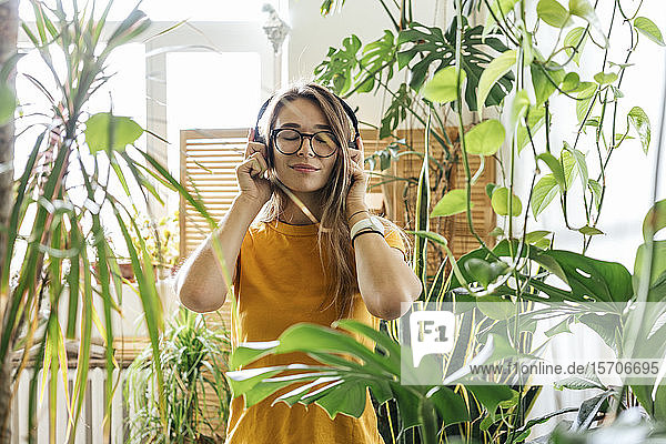 Young woman surrounded by plants listening to music with headphones