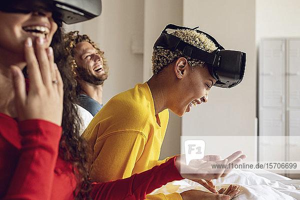 Glückliche Freunde haben Spaß mit VR-Brillen im Bett zu Hause