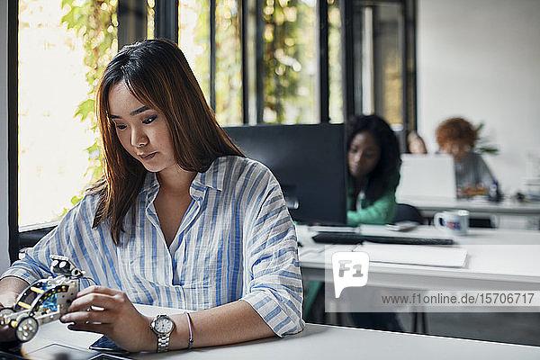 Geschäftsfrau hält Modellauto am Schreibtisch im Büro