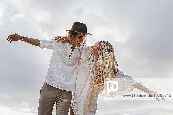 Glückliches junges Paar gegen den Himmel