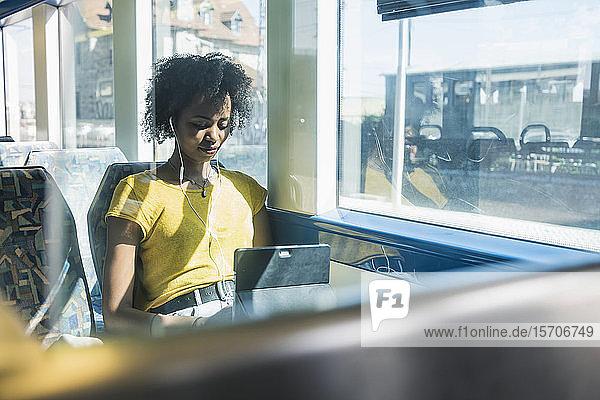 Junge Frau mit Kopfhörern mit Tablette im Zug