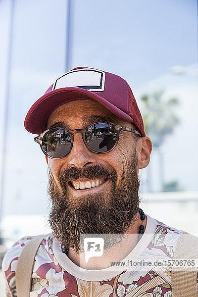 Lächelnder reifer Mann mit Bart  rotem Basecap und Sonnenbrille