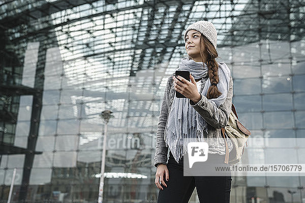 Junge Frau mit Smartphone wartet am Hauptbahnhof  Berlin  Deutschland