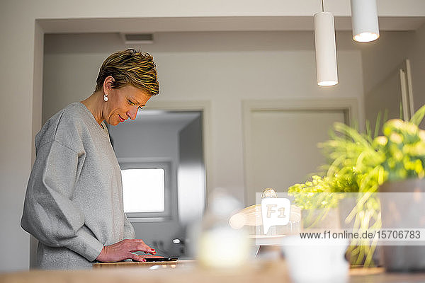 Woman using smartphone in kitchen at home