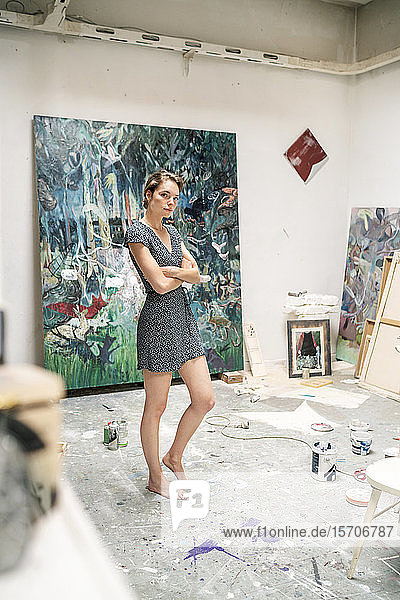 Young artist standing in her studio  with arms crossed