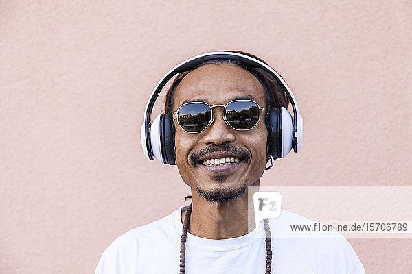 Porträt eines reifen Mannes mit Dreadlocks und Kopfhörern  der Musik hört