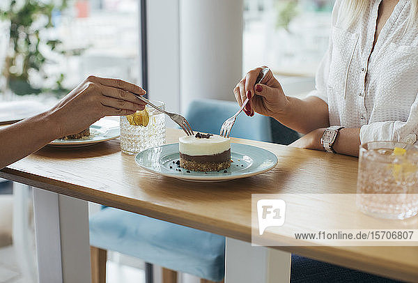 Anonymous young women sharing a cake at coffee shop