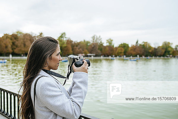 Woman standing at a lake taking a photo