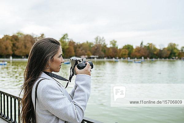 Frau steht an einem See und macht ein Foto