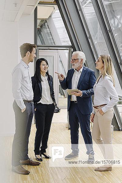 Lächelnde Geschäftsleute mit Tablette bei einer Besprechung im Büro