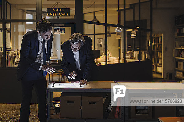 Two businesssmen with shining tablet talking in office