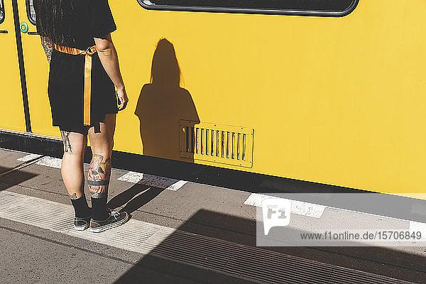 Rückenansicht und Schatten einer tätowierten jungen Frau  die am Bahnsteig steht  Berlin  Deutschland