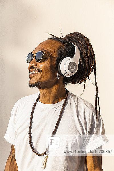 Porträt eines reifen Mannes mit Dreadlocks und Kopfhörern  der Musik hört und zur Seite schaut