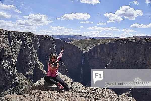 Glückliche Frau sitzt auf einem Hügel an den Maletsunyane-Fällen und nimmt ein Selfie  Lesotho