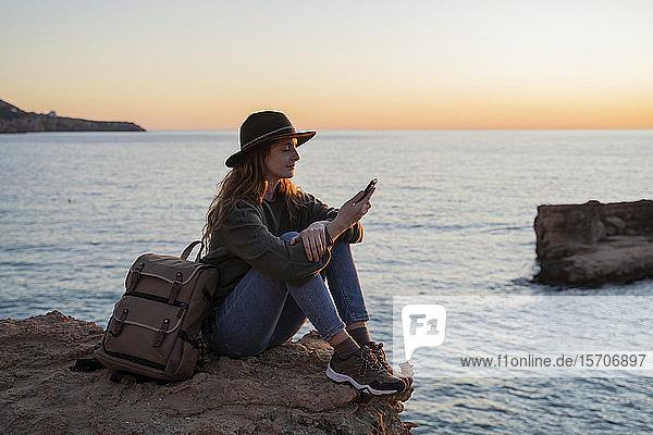 Junge Frau benutzt Smartphone am Strand bei Sonnenuntergang  Ibiza