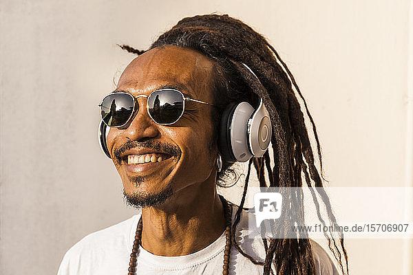 Porträt eines lächelnden reifen Mannes mit Dreadlocks und Kopfhörern  der Musik hört und zur Seite schaut