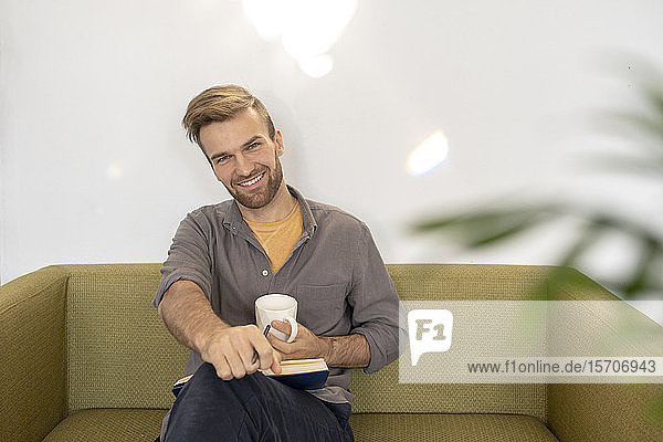 Portrait of smiling man sitting on couch with book and coffee cup