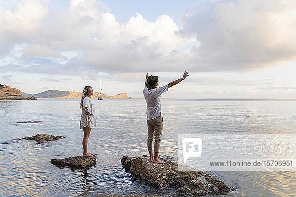 Auf Felsen vor dem Meer stehendes junges Paar  Ibiza  Balearen  Spanien